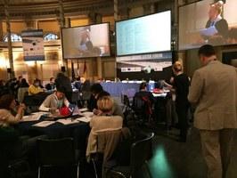 La moderatrice elenca le proposte dei partecipanti in streaming proiettate sullo schermo